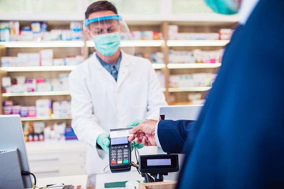 Patient, der eine Maske trägt, bezahlt in Apotheke kontaktlos mit Karte.
