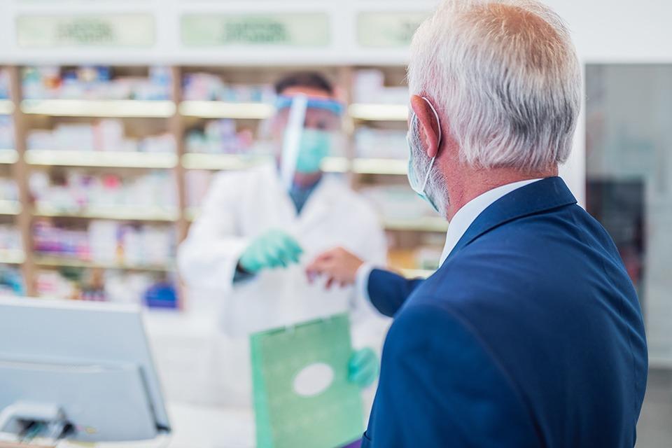 Älterer Patient erhält eine Tüte von einem Apotheker, beide tragen einen Mund-Nasen-Schutz.
