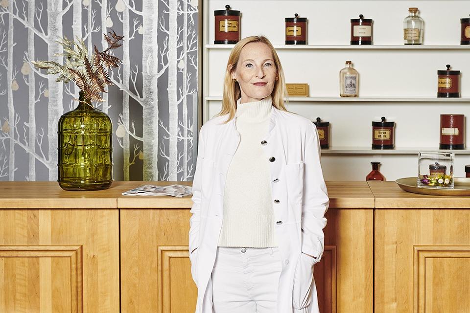Apothekerin Miriam Oster steht vor dem HV-Tisch in ihrer Apotheke. Im Hintergrund ist ein Regal mit historischen Arzneimittelbehältern zu sehen.
