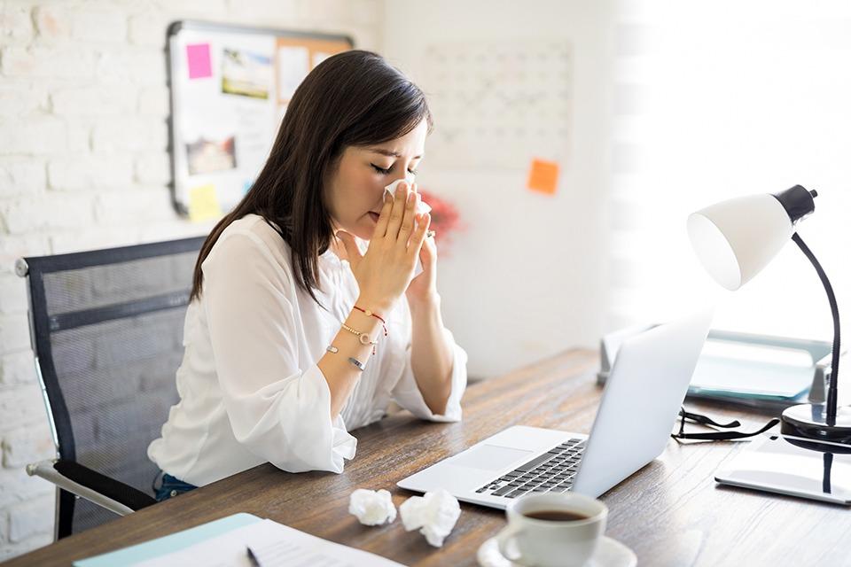 Junge Frau sitzt vor einem Laptop und putzt sich die Nase mit einem Papiertaschentuch. Vielleicht würde ihr jetzt ein Kombipräparat helfen.