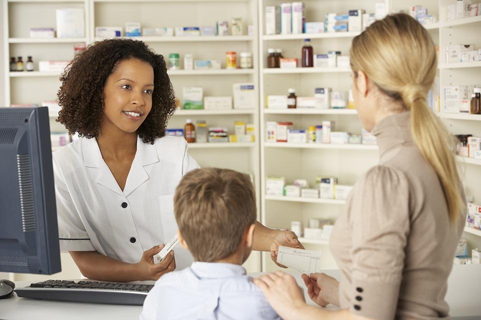 Apothekerin redet in einer Apotheke mit einer Mutter und ihrem Sohn.
