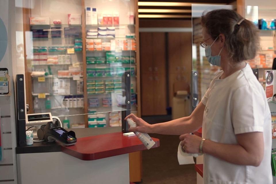 Mitarbeiterin in Apotheke reinigt den HV-Tisch mit einem Desinfektionspray und einem Tuch.