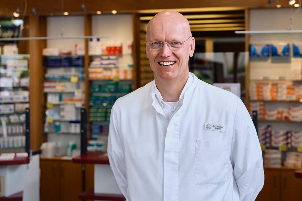 Apotheker Dr. Christian Mignat steht in seiner Apotheke. Er trägt einen weißen Kittel und lächelt freundlich in die Kamera.
