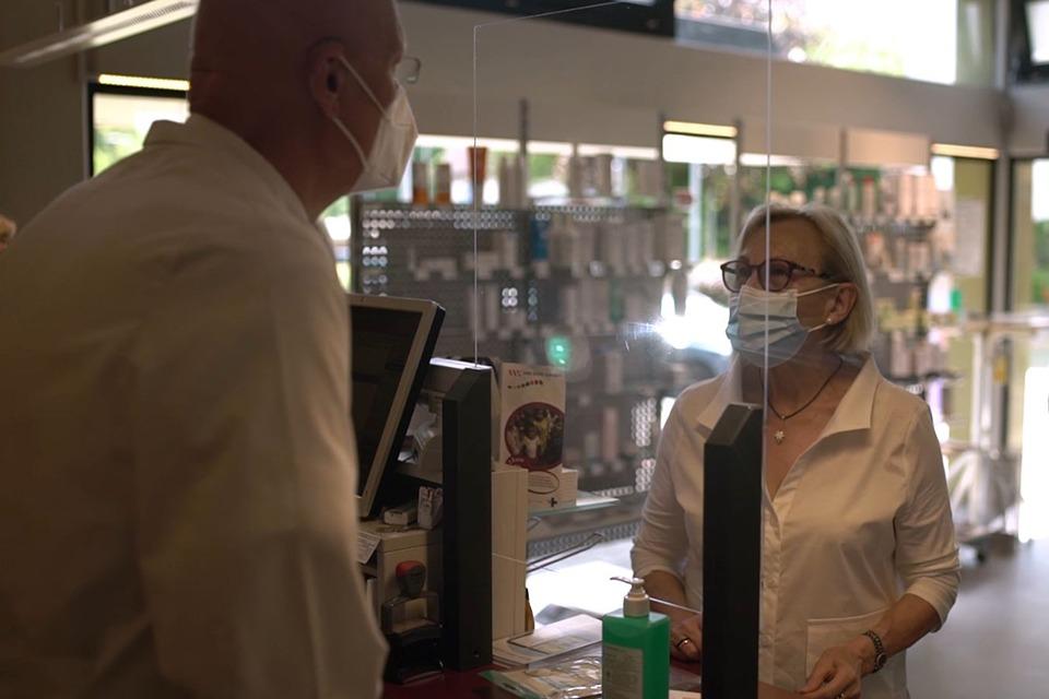 Apotheker berät Patientin in seiner Apotheke. Sie tragen beide eine medizinische Maske und sind durch eine Glasscheibe getrennt.